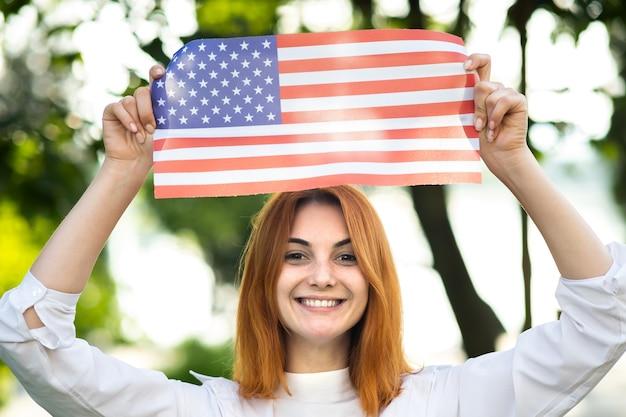 Portret szczęśliwej młodej rudowłosej kobiety trzymającej flagę narodową usa w dłoniach stojącej na zewnątrz