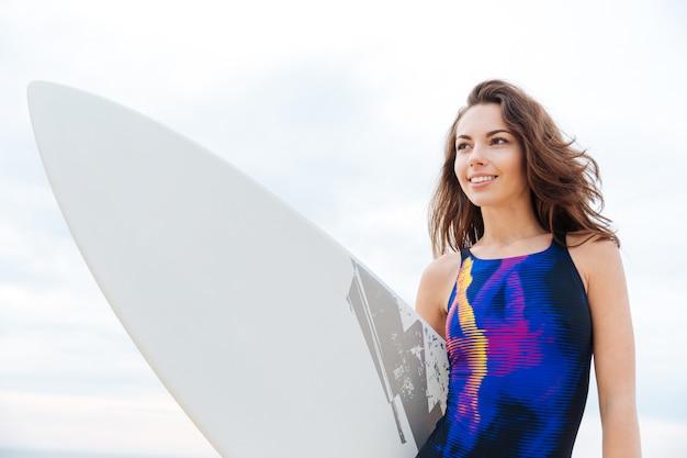 Portret szczęśliwej młodej surferki z białą deską surfingową