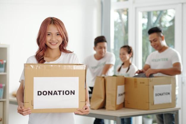 Portret szczęśliwej młodej wolontariuszki stojącej w centrum charytatywnym z tekturą darowizny w rękach