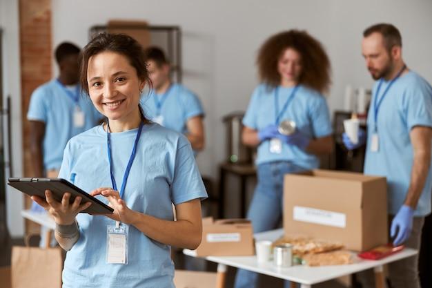 Portret szczęśliwej młodej wolontariuszki w niebieskim mundurze przy użyciu komputera typu tablet i uśmiecha się do kamery