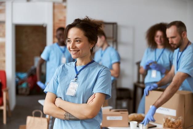 Portret szczęśliwej młodej wolontariuszki w niebieskim mundurze, uśmiechając się, stojąc z rękami