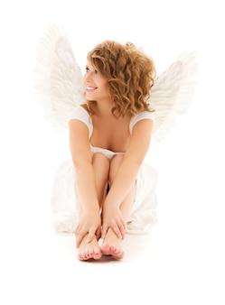 Portret szczęśliwej nastoletniej dziewczyny anioła na białej ścianie