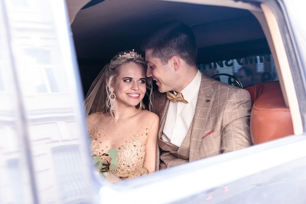 Portret szczęśliwej nowo poślubionej pary w samochodzie