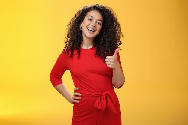 Portret szczęśliwej optymistycznej młodej kobiety z kręconymi włosami w czerwonej sukience, śmiejącej się radośnie, pokazującej kciuki w górę w aprobacie i jak gest, zachwyconej niesamowitym pomysłem, akceptującej plan nad żółtą ścianą.