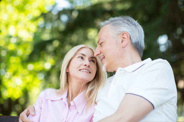 Portret szczęśliwej pary dojrzałych siedzi w parku
