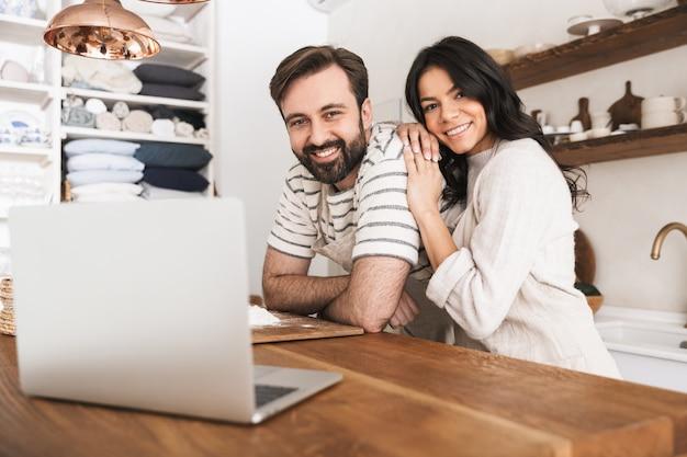 Portret szczęśliwej pary mężczyzny i kobiety w wieku 30 lat w fartuchach, patrząc na laptopa podczas gotowania ciasta w kuchni w domu