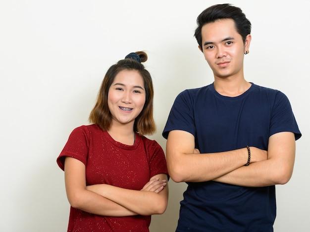 Portret szczęśliwej pary młodych azjatyckich uśmiecha się z rękami skrzyżowanymi razem