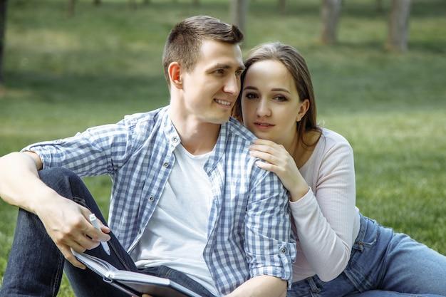 Portret szczęśliwej pary młodych korzystających dzień w parku razem