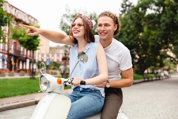Portret szczęśliwej pary młodych razem na motocyklu na ulicy miasta, wskazując palcem