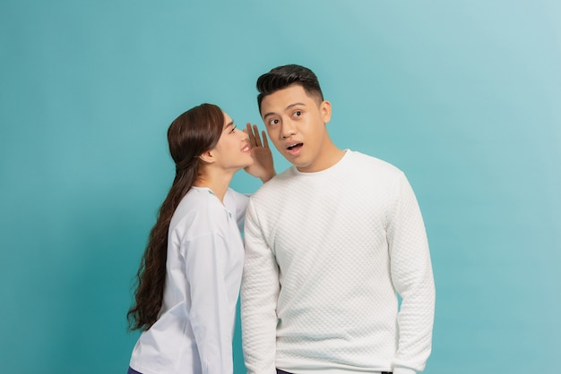 Portret szczęśliwej pary młodych stojących razem na niebiesko, mówiąc tajemnice