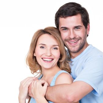 Portret szczęśliwej pary obejmującej w dorywczo - na białym tle