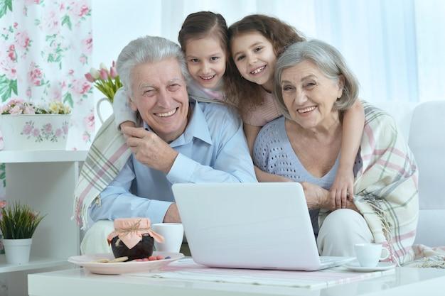 Portret szczęśliwej pary seniorów z wnukami i laptopem w domu