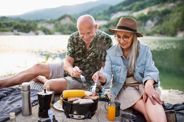 Portret szczęśliwej pary starszych odpoczynku na letnie wakacje, grill nad jeziorem.