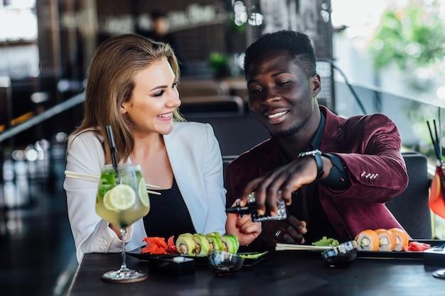 Portret szczęśliwej pary zabawy podczas jedzenia rolek sushi w restauracji na nowoczesnym tarasie.