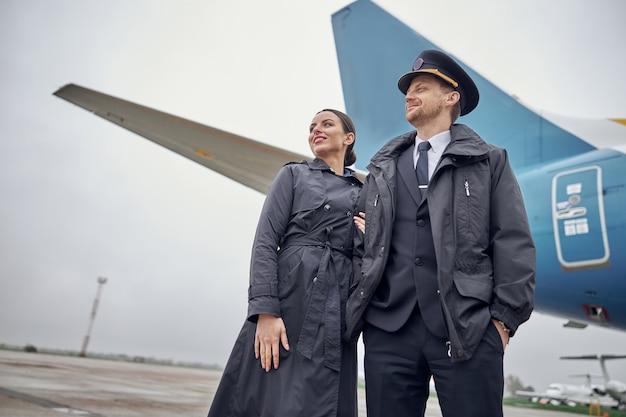 Portret szczęśliwej pewnej kaukaskiej załogi samolotu w pobliżu samolotu