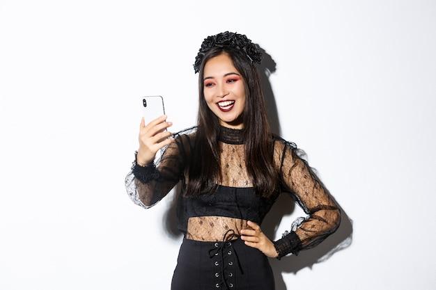 Portret szczęśliwej pięknej azjatyckiej kobiety w kostiumie na halloween uśmiechając się i patrząc na ekran telefonu komórkowego, mając połączenie wideo, stojąc na białej ścianie