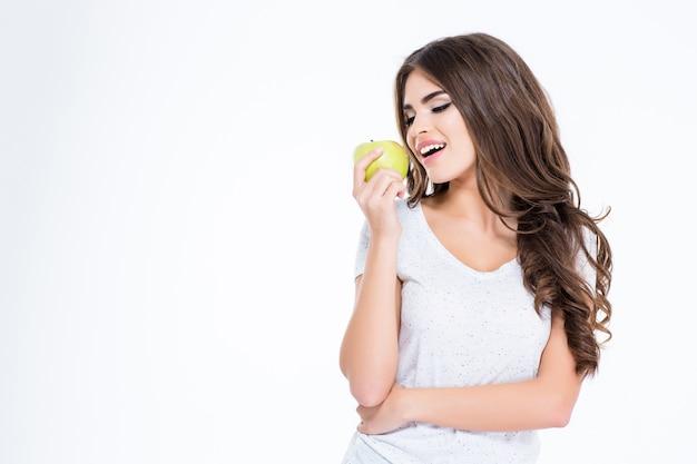 Portret szczęśliwej pięknej kobiety jedzącej jabłko na białej ścianie