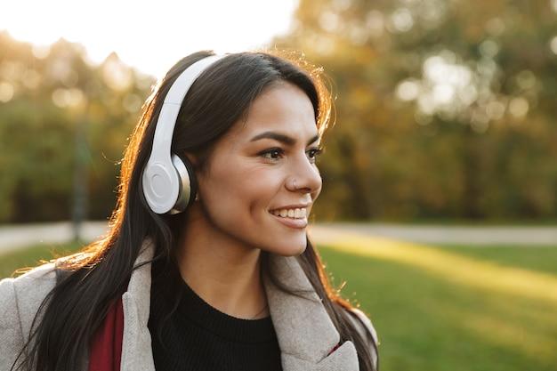 Portret szczęśliwej pięknej kobiety w płaszczu słuchającej muzyki przez słuchawki i uśmiechającej się podczas spaceru w jesiennym parku