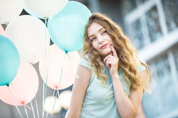 Portret szczęśliwej pięknej kobiety z latającymi wielokolorowymi balonami w mieście
