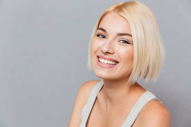 Portret szczęśliwej pięknej młodej kobiety z blond włosami na szarej ścianie