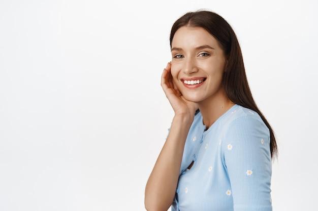 Portret szczęśliwej pięknej modelki, uśmiechnięte białe zęby, dotykające policzka, reklama produktów do pielęgnacji skóry, kosmetyków lub makijażu, stojąca na białym tle.