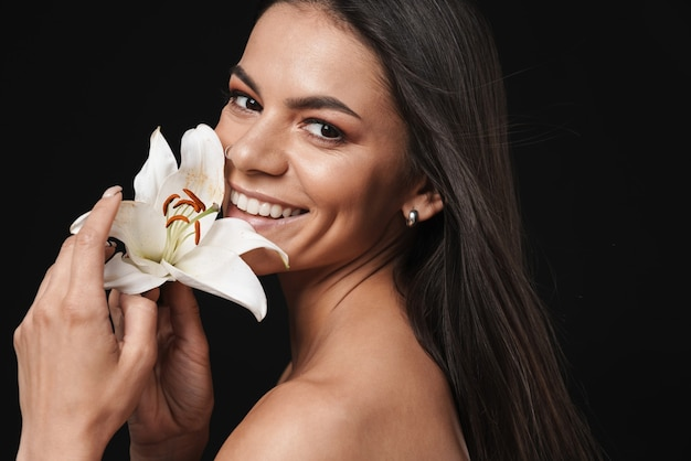 Portret szczęśliwej podekscytowanej młodej pięknej nagiej kobiety pozującej na białym tle nad czarną ścianą z kwiatem
