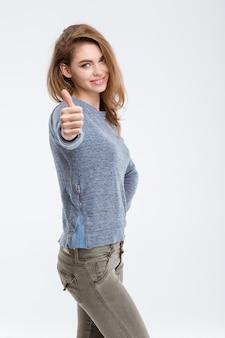 Portret szczęśliwej przypadkowej kobiety pokazującej kciuk na białym tle na białym tle