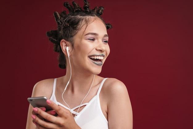 Portret szczęśliwej punkowej dziewczyny z dziwaczną fryzurą i ciemną szminką, śmiejąc się podczas korzystania ze smartfona ze słuchawkami izolowanymi na czerwonej ścianie