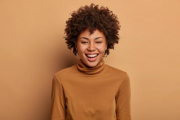 Portret szczęśliwej radosnej ciemnoskórej kobiety uśmiecha się szeroko, ma białe, idealne zęby, wyraża radość, czuje się szczęśliwie w pozytywny dzień, nosi sweter z poloneck, pozuje na brązowej ścianie