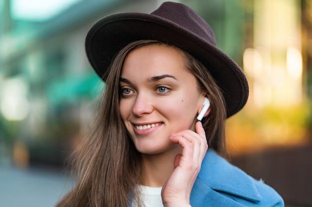 Portret szczęśliwej radosnej stylowej modnej brunetki modnej kobiety w kapeluszu z bezprzewodowymi białymi słuchawkami cieszy się i słucha muzyki w centrum miasta. współczesny styl życia i technologia