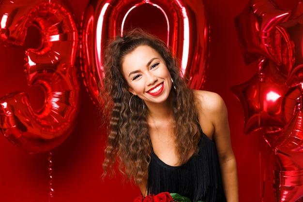 Portret szczęśliwej rocznej kobiety na czerwonym tle z czerwonymi balonami piękna dziewczyna kaukaska ...