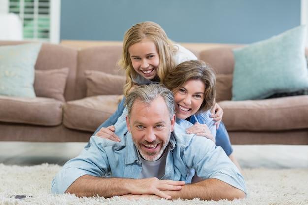 Portret szczęśliwej rodziny leżącej sterty na dywanie w salonie