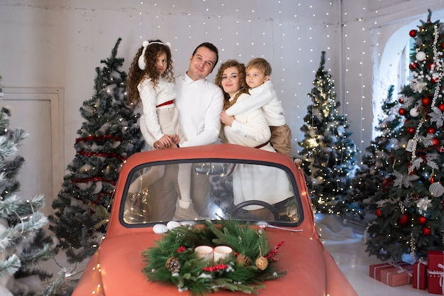 Portret szczęśliwej rodziny. matka, ojciec i małe dzieci w czerwonym samochodzie w pobliżu choinek.