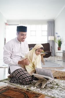 Portret szczęśliwej rodziny muzułmańskiej z dziećmi, czytając koran i modląc się razem w domu