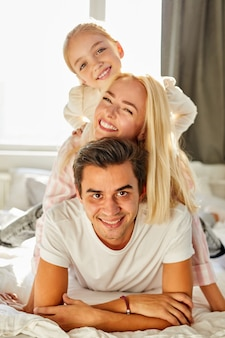Portret szczęśliwej rodziny na łóżku, odpoczywają, cieszą się razem rano w domu