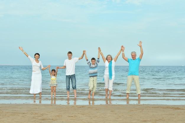 Portret szczęśliwej rodziny na plaży latem z podniesionymi rękami