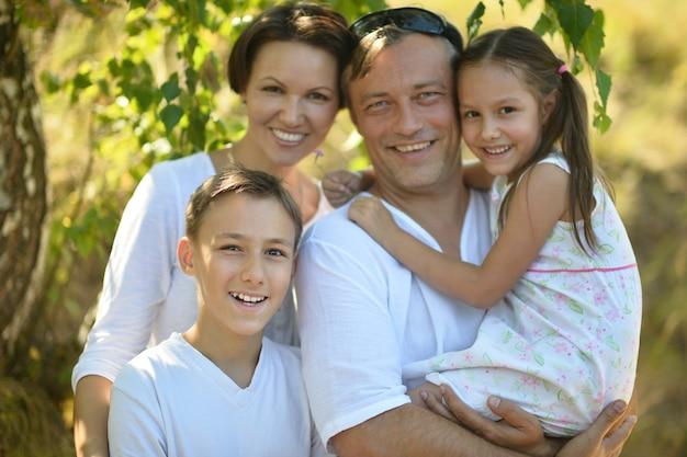 Portret szczęśliwej rodziny odpoczywającej w letnim parku