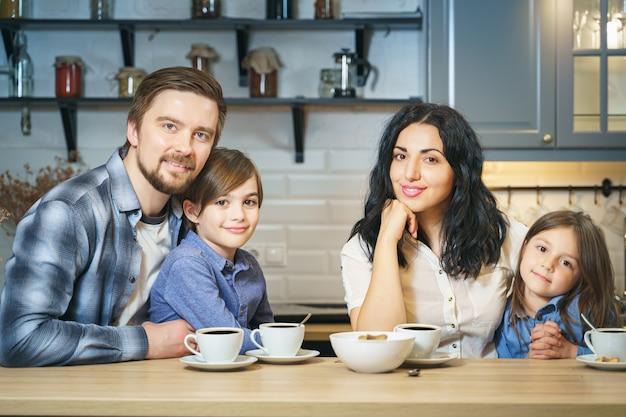 Portret szczęśliwej rodziny picia herbaty z ciasteczkami w kuchni.