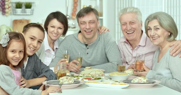 Portret szczęśliwej rodziny przy stole ze smacznym jedzeniem