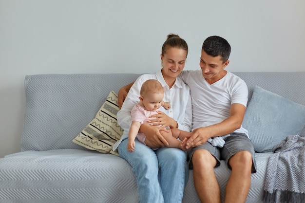 Portret szczęśliwej rodziny siedzącej na kanapie w salonie, ludzie noszący zwykłe ubrania, spędzający czas z niemowlęciem w domu, rodzicielstwo, dzieciństwo.
