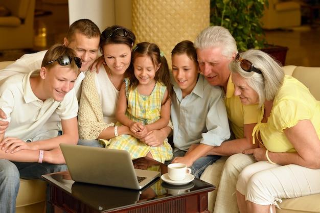 Portret szczęśliwej rodziny siedzącej z laptopem