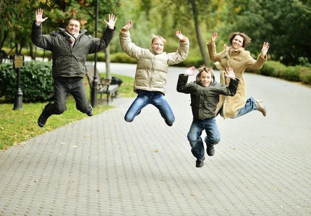 Portret szczęśliwej rodziny skaczącej w jesiennym parku