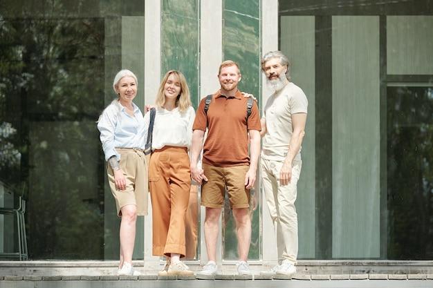 Portret szczęśliwej rodziny składającej się ze starszych dzieci i starszych rodziców stojących przed pięknym domkiem ze szklaną ścianą