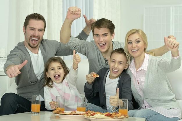 Portret szczęśliwej rodziny w domu z pizzą