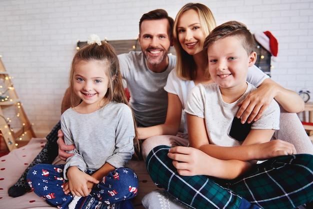 Portret szczęśliwej rodziny w łóżku na boże narodzenie