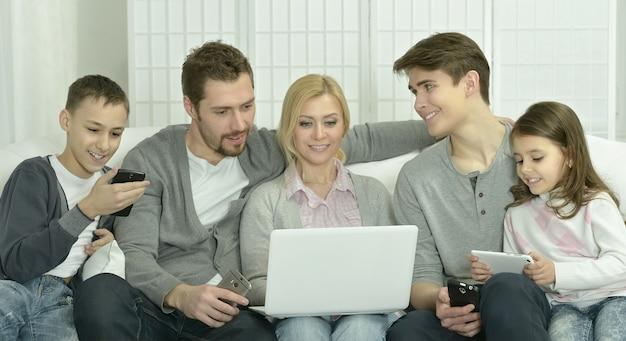 Portret szczęśliwej rodziny z elektronicznymi gadżetami w domu