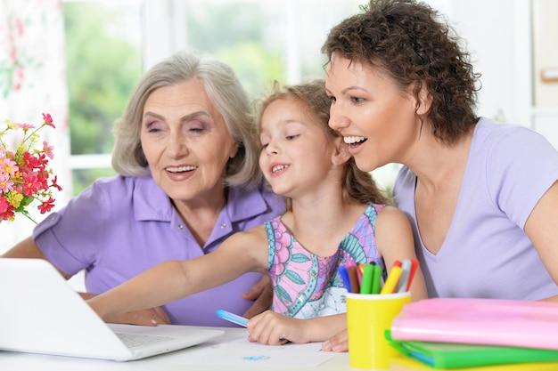 Portret szczęśliwej rodziny z laptopem w domu