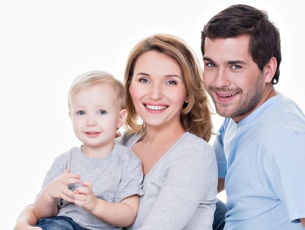 Portret szczęśliwej rodziny z małym dzieckiem patrząc na kamery - na białym tle