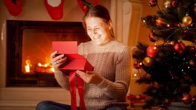 Portret szczęśliwej roześmianej młodej kobiety patrzącej do wnętrza świecącego świątecznego pudełka, siedząc na podłodze przy kominku