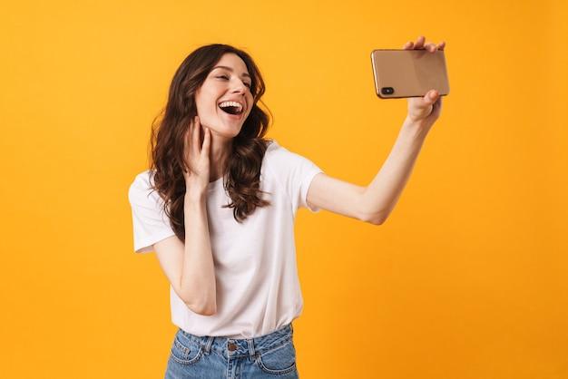 Portret szczęśliwej roześmianej optymistycznie uśmiechniętej młodej kobiety pozującej na białym tle nad żółtą ścianą, weź selfie przez telefon komórkowy
